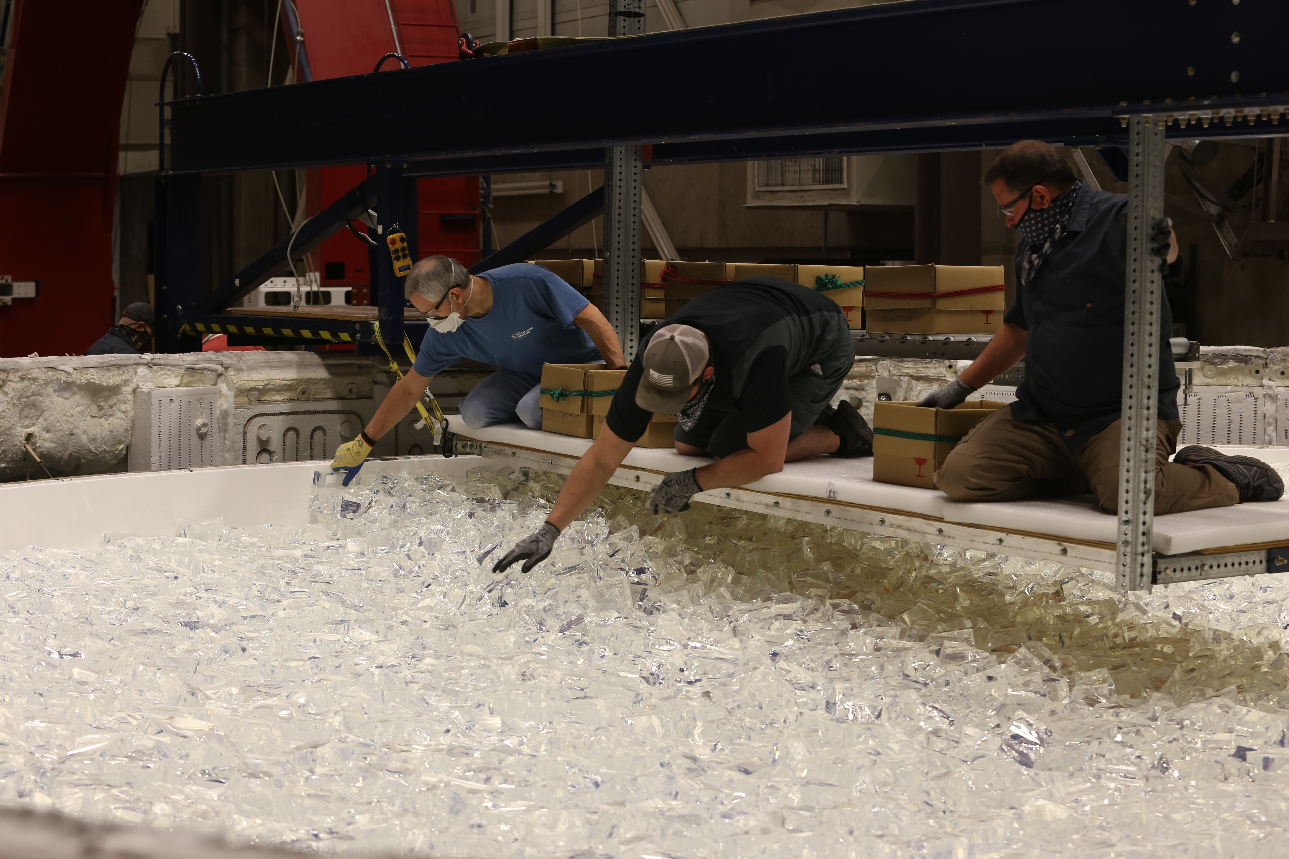 Engineers at the Richard F. Caris Mirror Lab hand-load chunks of glass into the mold. Almost 20 tons of glass are added this way before the lid will be closed and the furnace fired up to melt the glass.